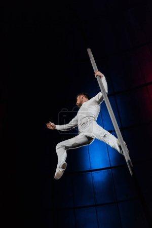 Photo pour Vue à faible angle de l'acrobate posant tout en exécutant et en tenant un poteau métallique - image libre de droit