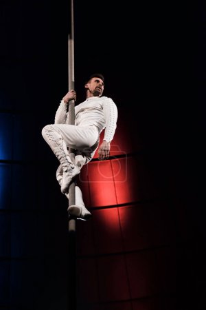 Photo for Low angle view of strong acrobat holding metallic pole while performing in circus - Royalty Free Image