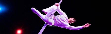 Photo pour Prise de vue panoramique d'un beau acrobate tenant un poteau métallique tout en jouant au cirque - image libre de droit