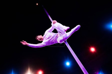 back light near handsome acrobat holding metallic pole while performing in circus