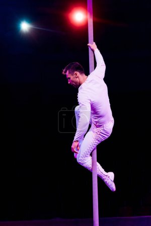 Photo for Acrobat holding pole while performing near red and blue back light on black - Royalty Free Image