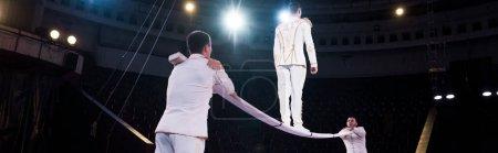 Photo pour Plan panoramique d'acrobates soutenant l'homme marchant sur un poteau métallique dans un cirque - image libre de droit