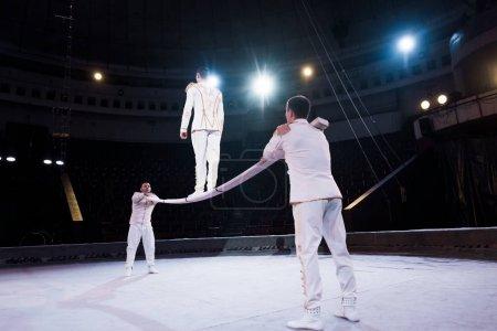Photo pour Acrobates soutenir l'homme marchant sur le poteau métallique dans le cirque - image libre de droit