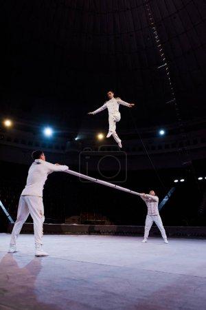 Photo pour Acrobates tenant la pole près de gymnaste sautant dans le cirque - image libre de droit