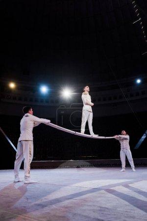 Photo pour Gymnaste debout sur le poteau près des acrobates dans le cirque - image libre de droit