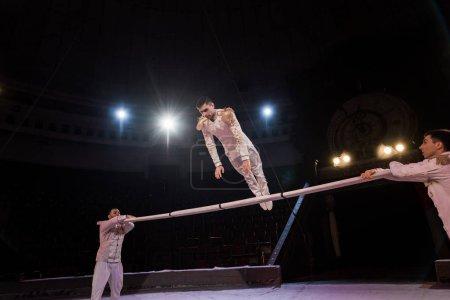 Photo pour Gymnaste beau exercice sur la pole près des acrobates dans le cirque - image libre de droit