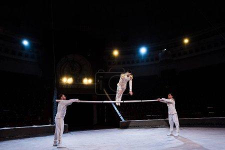 Photo pour Gymnaste flexible faisant de l'exercice sur un poteau près d'acrobates au cirque - image libre de droit