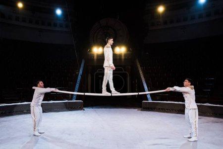 Photo pour Vue latérale de gymnaste faisant de l'exercice sur un poteau près d'acrobates au cirque - image libre de droit