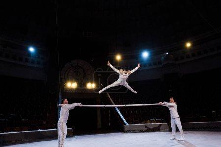 Photo pour Gymnaste avec les mains tendues sautant sur la pole près des acrobates dans le cirque - image libre de droit