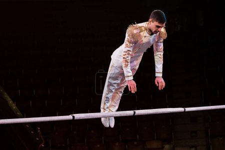 handsome gymnast exercising near pole in arena of circus