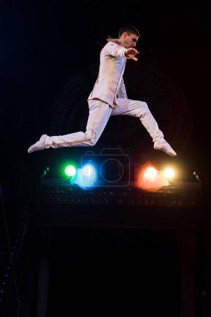 Photo pour Vue latérale d'acrobate aérien flexible volant dans l'arène du cirque - image libre de droit