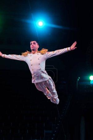 Photo pour Acrobate aérien beau avec les mains tendues volant dans l'arène du cirque - image libre de droit