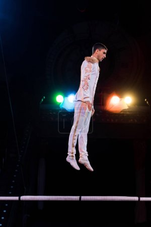 Photo for Handsome gymnast balancing near pole in arena of circus - Royalty Free Image