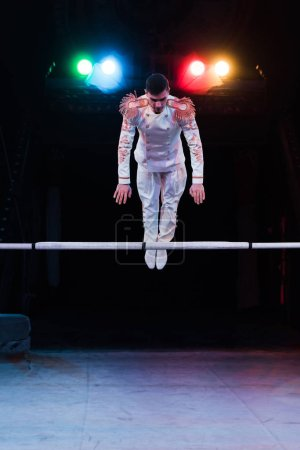 Photo for Handsome gymnast in costume balancing near pole in arena of circus - Royalty Free Image
