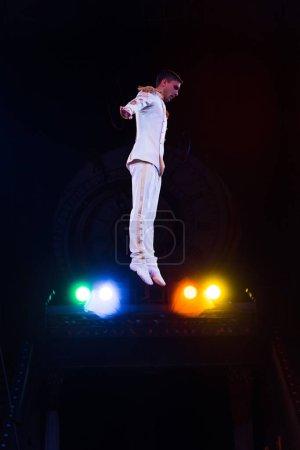 Photo pour Vue latérale du beau gymnaste en costume sautant dans l'arène du cirque - image libre de droit