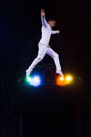 Photo pour Vue latérale du beau gymnaste avec les mains tendues sautant dans l'arène du cirque - image libre de droit