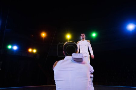 Photo pour Vue de dos de l'homme debout près de acrobate effectuant dans le cirque - image libre de droit