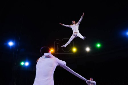 Photo for Low angle view of handsome air acrobat with outstretched hands jumping near pole in arena of circus - Royalty Free Image