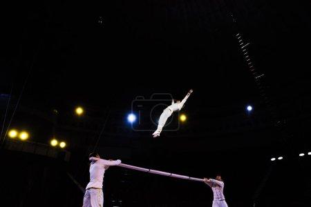 Photo pour Vue à faible angle de acrobate aérien sautant près du pôle et des hommes dans le cirque - image libre de droit