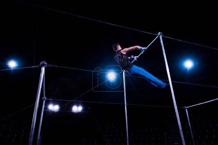 Photo pour Vue à angle bas de gymnaste exécutant sur des barres horizontales dans l'arène du cirque - image libre de droit