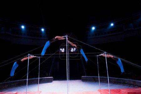 Photo pour Quatre gymnastes jouant sur des barres horizontales au cirque - image libre de droit