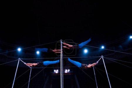 Photo pour Quatre acrobates se produisant sur des barres horizontales au cirque - image libre de droit