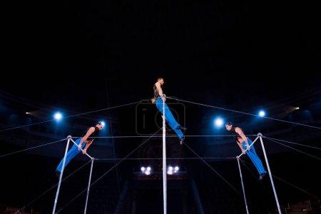 Photo pour Vue à faible angle des gymnastes exécutant sur des barres horizontales dans le cirque - image libre de droit
