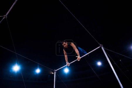 Photo pour Vue à faible angle d'acrobate beau performant sur des barres horizontales dans le cirque - image libre de droit