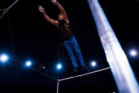 Photo pour Foyer sélectif de gymnaste beau performant sur les barres horizontales dans le cirque - image libre de droit