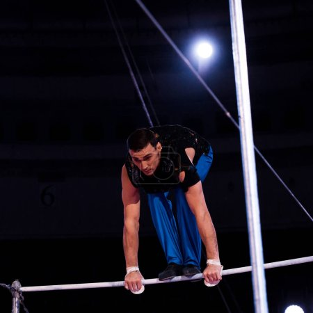 Photo for Athletic gymnast performing on horizontal bars in arena of circus - Royalty Free Image