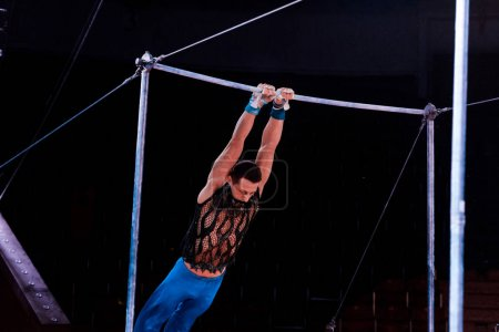 Photo for Athletic man performing on horizontal bars in arena of circus - Royalty Free Image