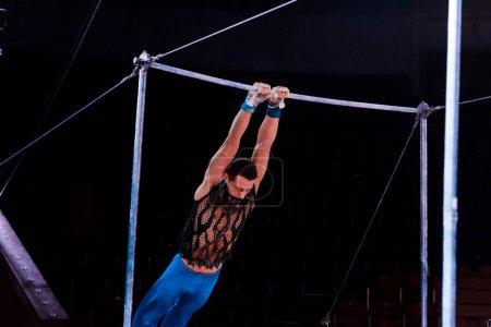 Foto de El hombre atlético que actúa en las barras horizontales en la arena del circo - Imagen libre de derechos