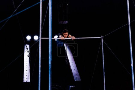 Photo for Athletic acrobat performing on horizontal bars in arena of circus - Royalty Free Image