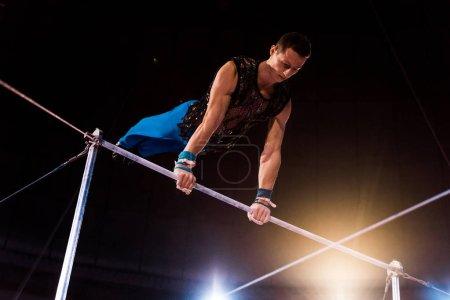 Foto de Gimnasia deportiva actuando en las barras horizontales en la arena del circo. - Imagen libre de derechos