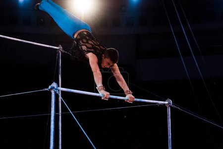 Photo for Athletic gymnast exercising on horizontal bars in arena of circus - Royalty Free Image