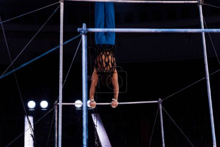 Photo for Back view of athletic gymnast performing on horizontal bars in arena of circus - Royalty Free Image
