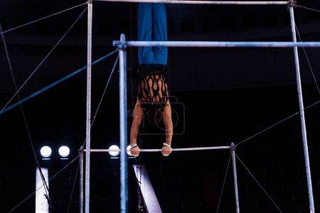 Foto de Vista trasera del gimnasia atlética actuando en las barras horizontales en la arena del circo. - Imagen libre de derechos