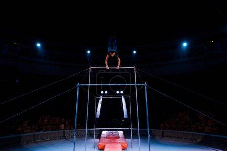 Foto de Gimnasia bonita y deportiva actuando en las barras horizontales en la arena del circo. - Imagen libre de derechos