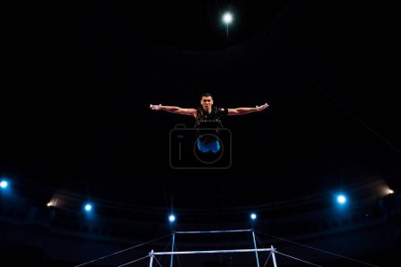 Photo for Athletic gymnast with outstretched hands in arena of circus - Royalty Free Image