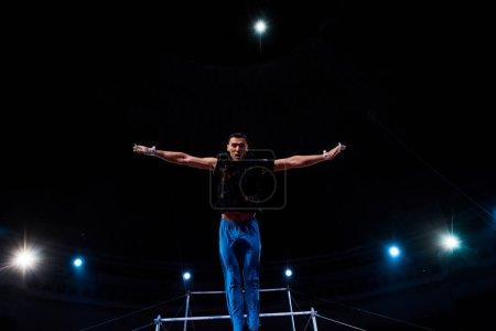 Foto de Gimnasia deportiva con manos extendidas actuando cerca de las barras horizontales en la arena del circo. - Imagen libre de derechos