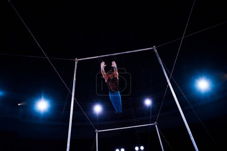 Photo for Athletic gymnast jumping while performing on horizontal bars in arena of circus - Royalty Free Image