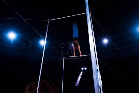 Photo for Back view of acrobat performing on horizontal bars in arena of circus - Royalty Free Image