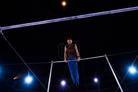 Photo for Low angle view of athletic gymnast performing on horizontal bars in arena of circus - Royalty Free Image