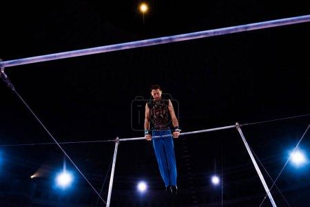 Foto de Vista de bajo ángulo del gimnasia deportiva que actúa en las barras horizontales en la arena del circo. - Imagen libre de derechos