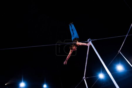 Photo for Low angle view of athletic man performing on horizontal bars in arena of circus - Royalty Free Image