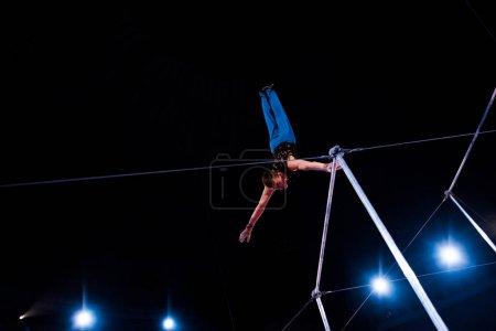 Foto de Vista de bajo ángulo del deportista que actúa en las barras horizontales en la arena del circo. - Imagen libre de derechos