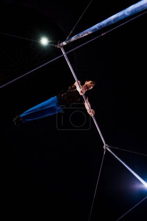 Photo for Bottom view of athletic gymnast performing on horizontal bars in arena of circus - Royalty Free Image