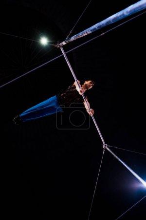 Foto de Vista inferior del gimnasia atlética actuando en las barras horizontales en la arena del circo. - Imagen libre de derechos