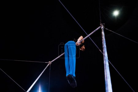 Photo for Low angle view of flexible gymnast performing on horizontal bars in arena of circus - Royalty Free Image