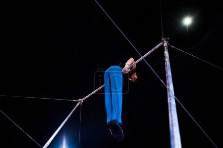 Foto de Vista de bajo ángulo de gimnasia flexible actuando en barras horizontales en la arena del circo. - Imagen libre de derechos